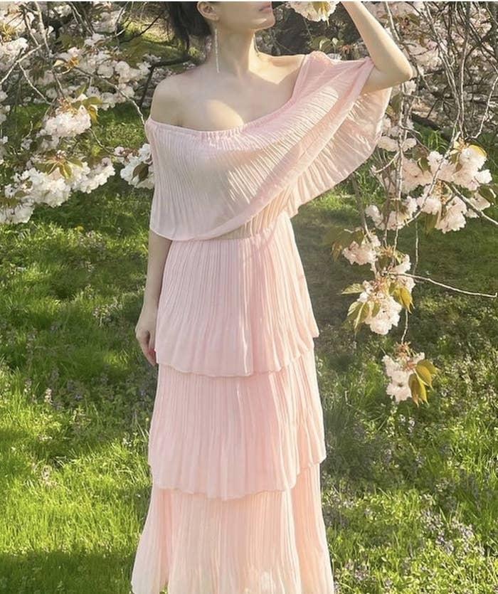 A reviewer wearing an off the shoulder pink ruffle dress