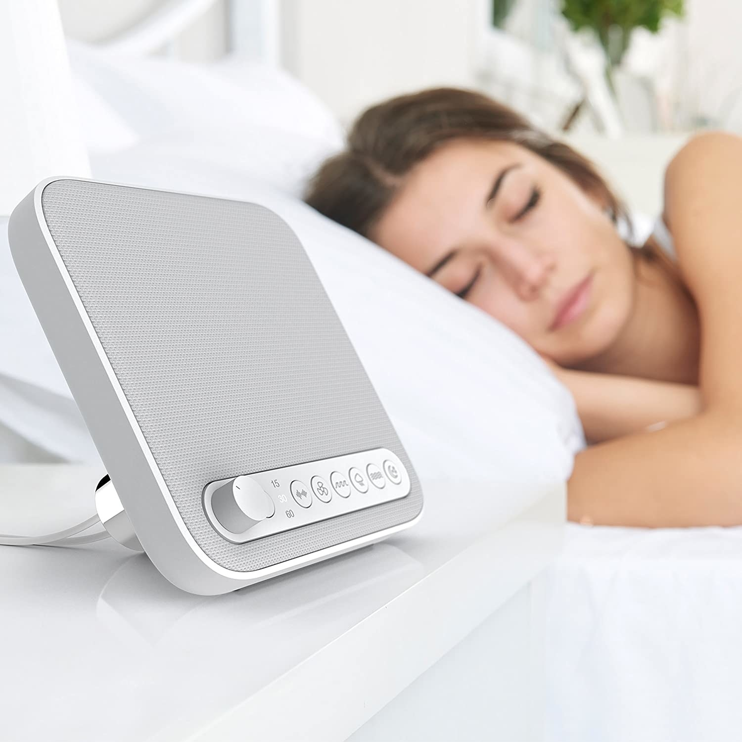 Sleep therapy sound machine placed on bedside table in front of sleeping model