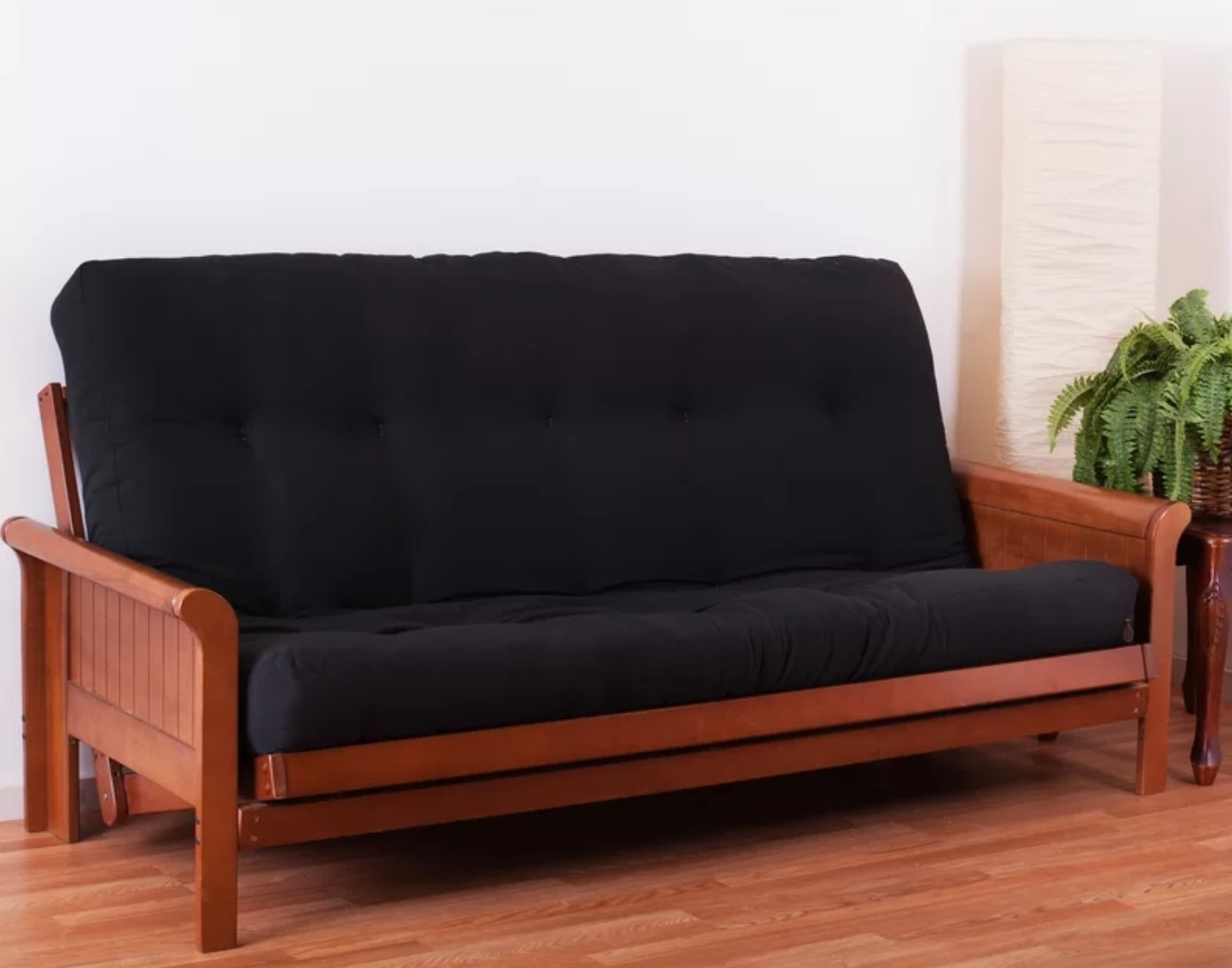 the foam futton in black with a wood frame