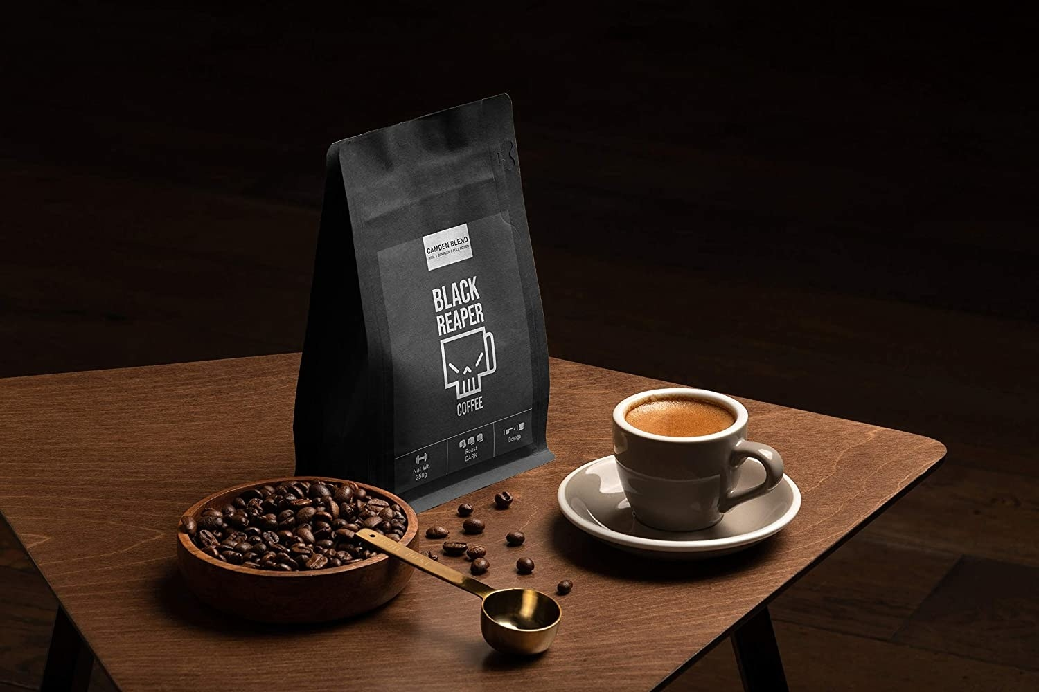 A packet of Black Reaper on a table with a cup of coffee and some coffee beans in a bowl next to it.
