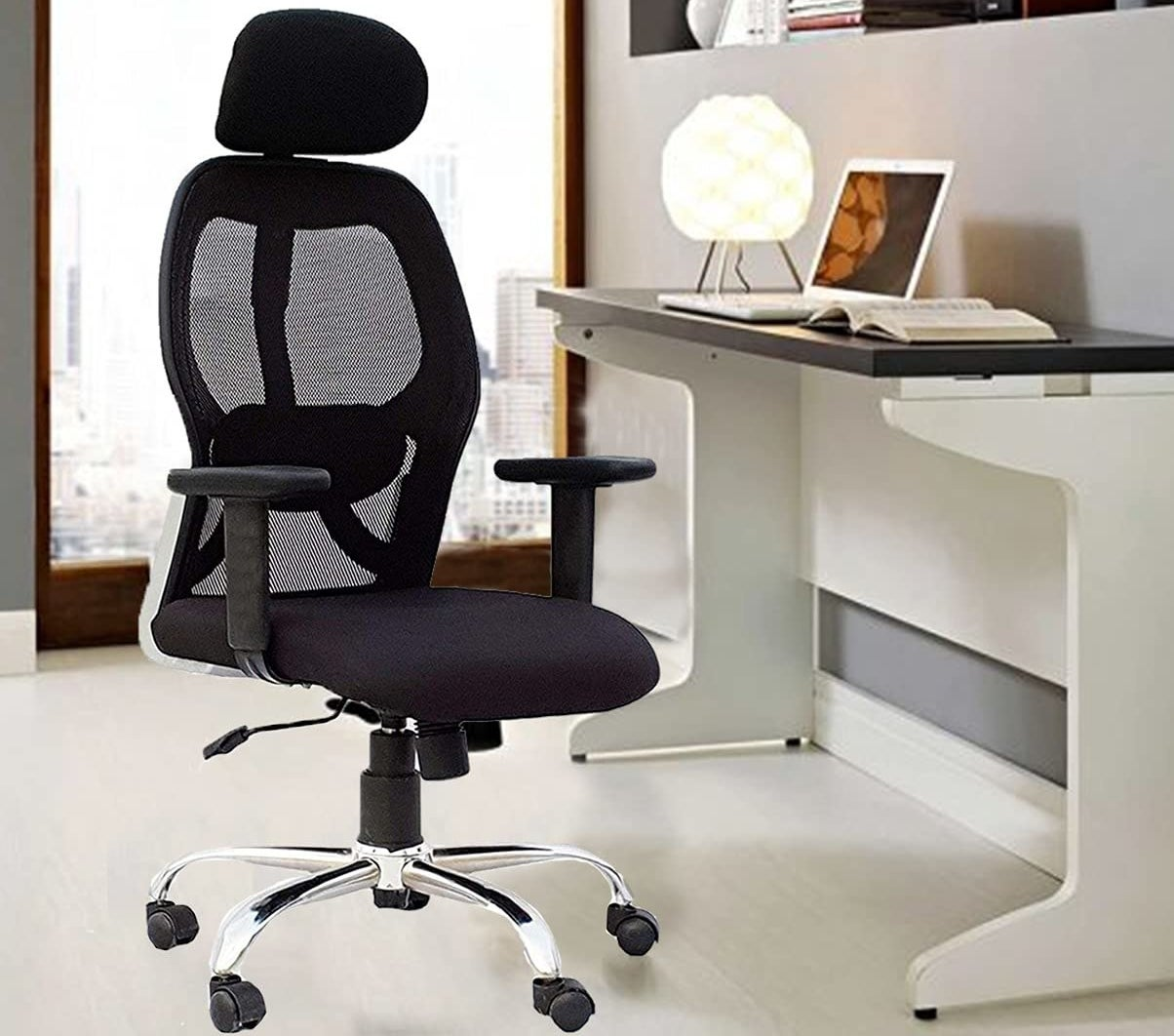 An ergonomic desk chair in a room with a work desk in front of it.