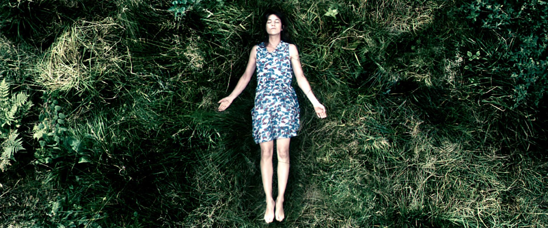 a woman lying in a grassy field