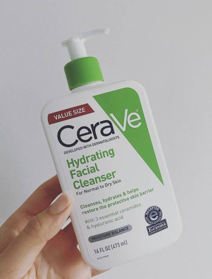 a person holding the green and white cleanser bottle