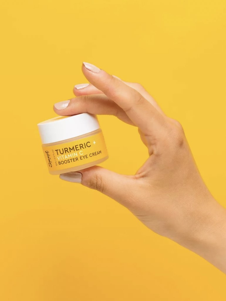 a hand holding a yellow jar of the eye cream