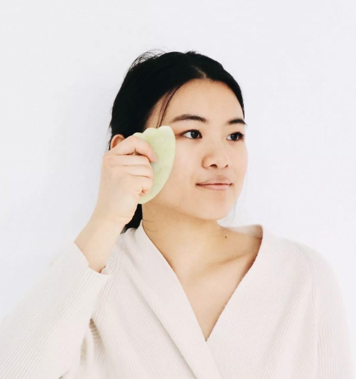 a person using a jade gua sha tool on their cheek