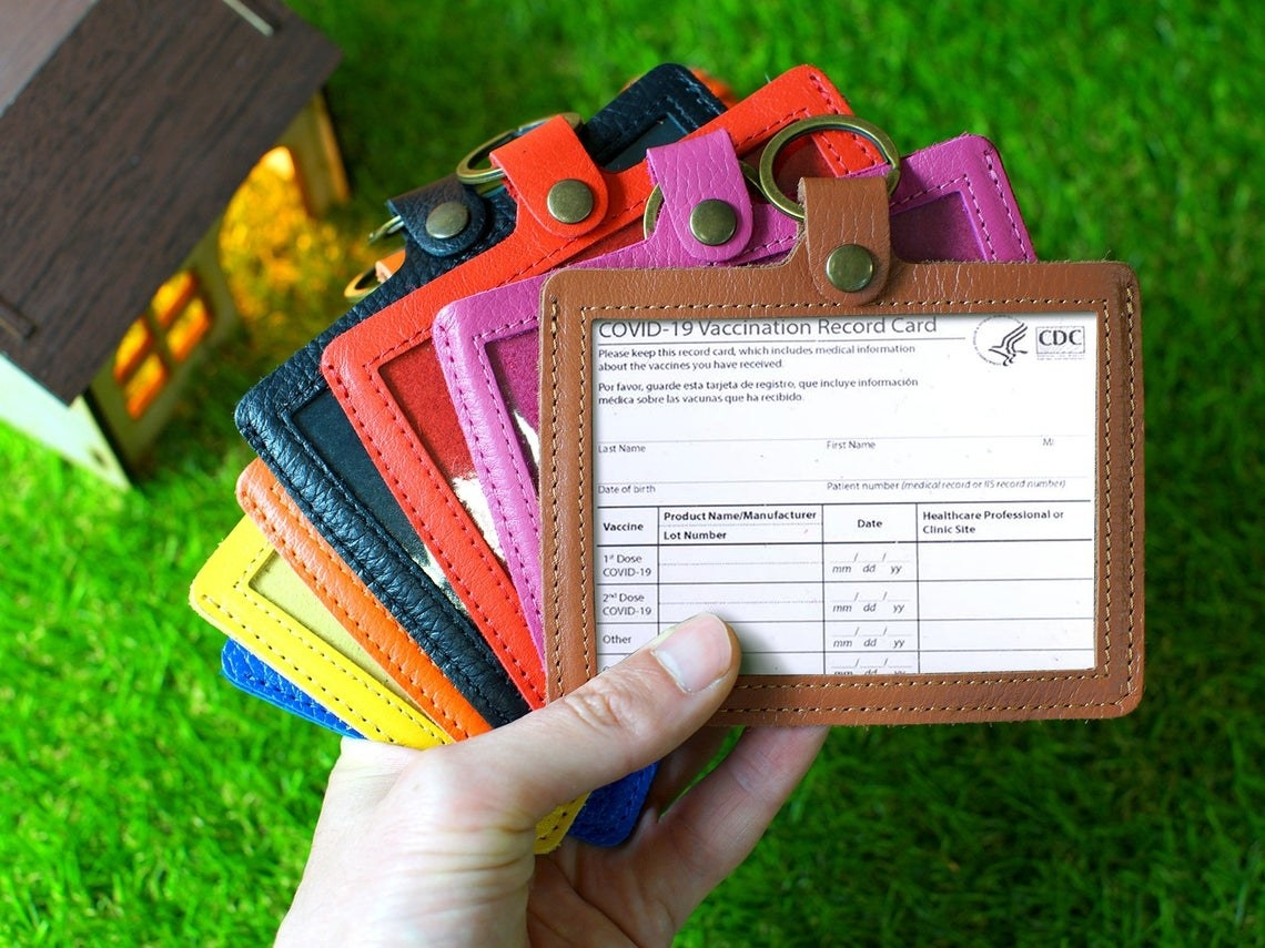A person holding all the color options of the vaccine card holder