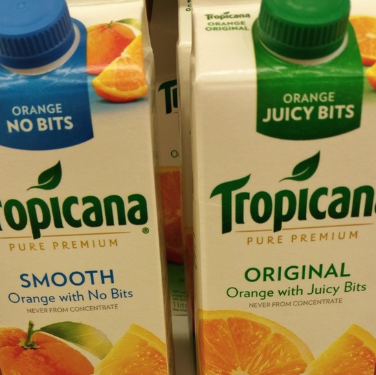 """Two boxes of orange juice; the left one says """"smooth orange with no bits"""" and the right one says """"original orange with juicy bits"""""""