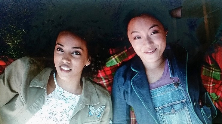 Janet and Samira are lying face up on a red and green plaid picnic blanket in Grange Park