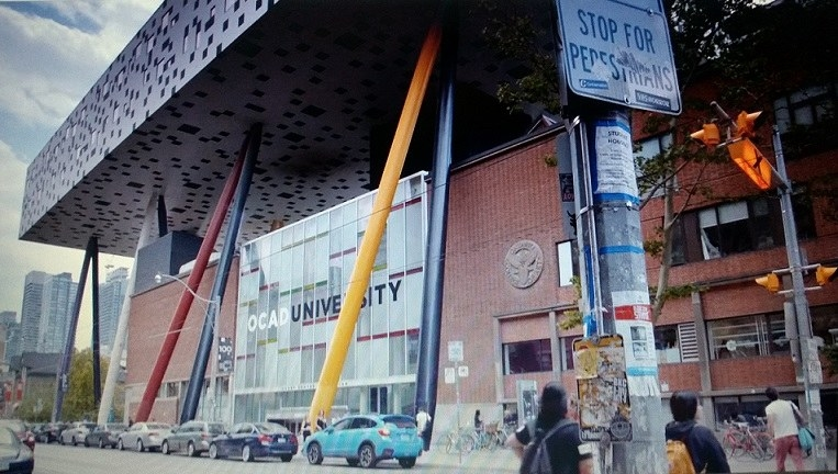 The brick OCAD University building is being upheld by blue, red, yellow and black supporting structures