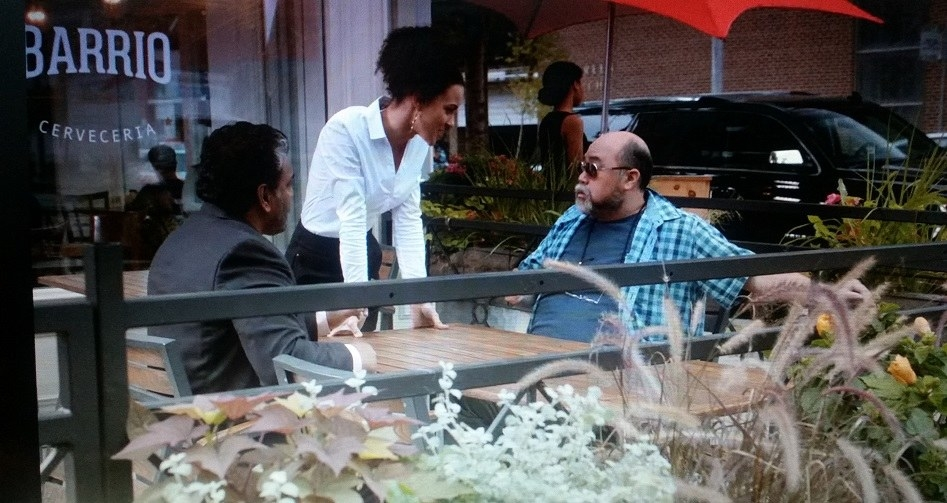 Appa and Mr. Mehta sit on the patio and talk amongst themselves until a server comes over to tell them something