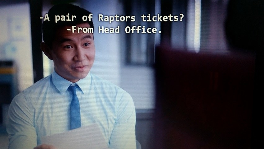 Jung wearing a dress shirt and tie is incredulous about receiving a pair of Raptors tickets