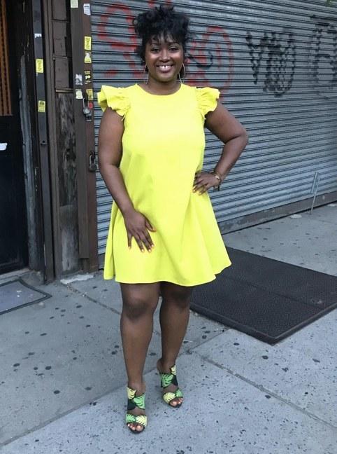 A reviewer wearing a yellow ruffle sleeve dress