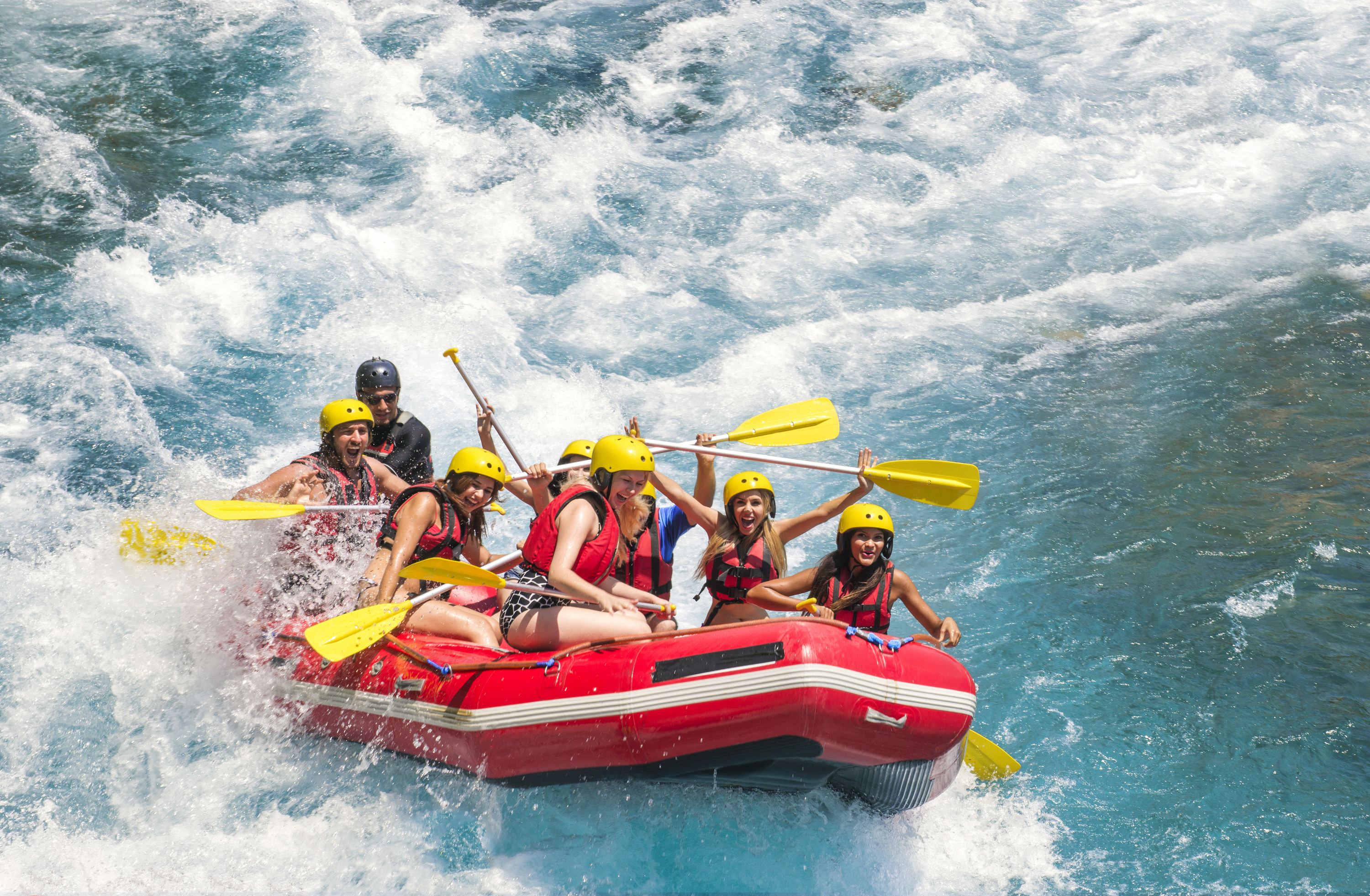 A group of friends white water rafting; they smile as they hurdle down a thunderous part of the river.