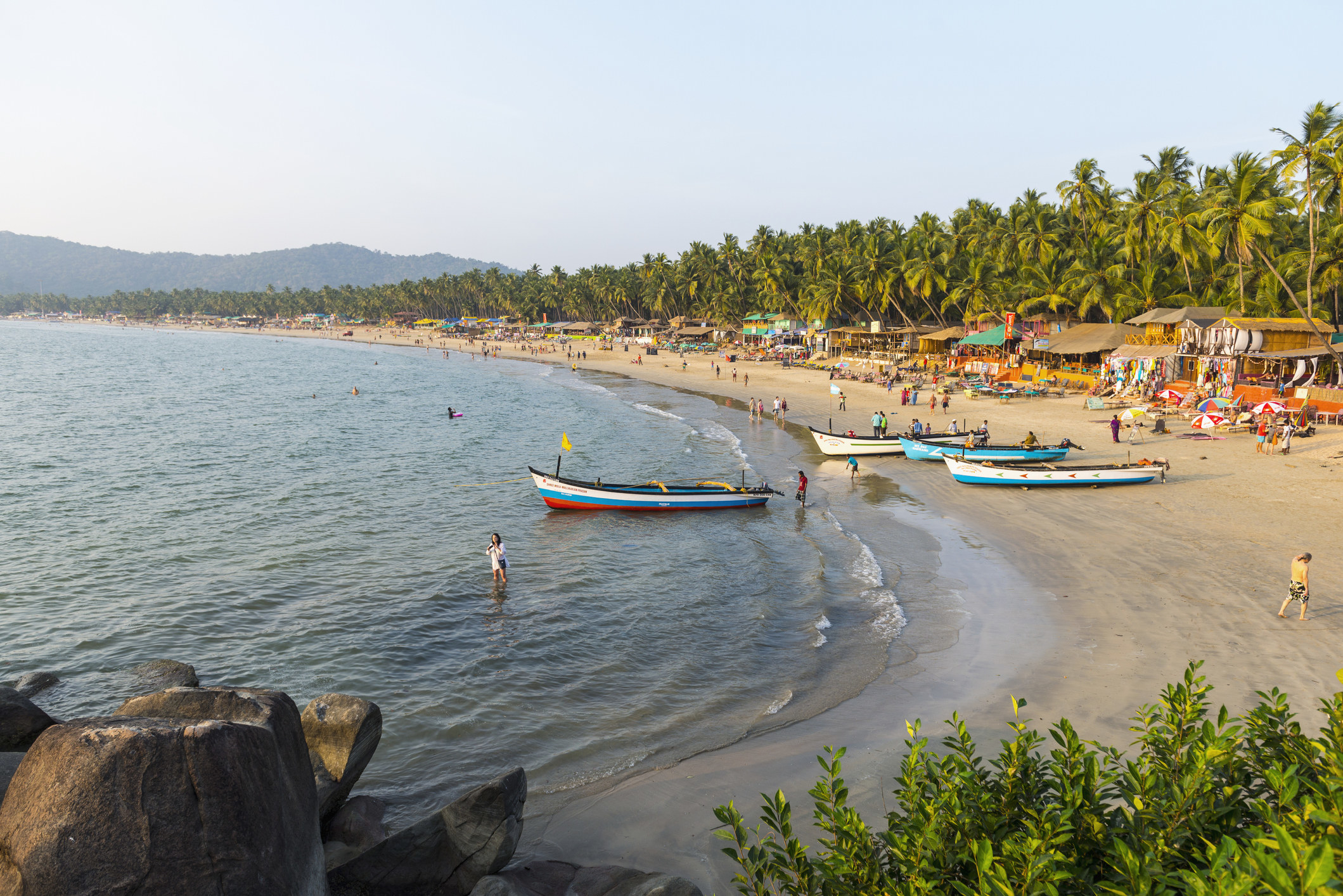 A beach with boats and people in Goa, India