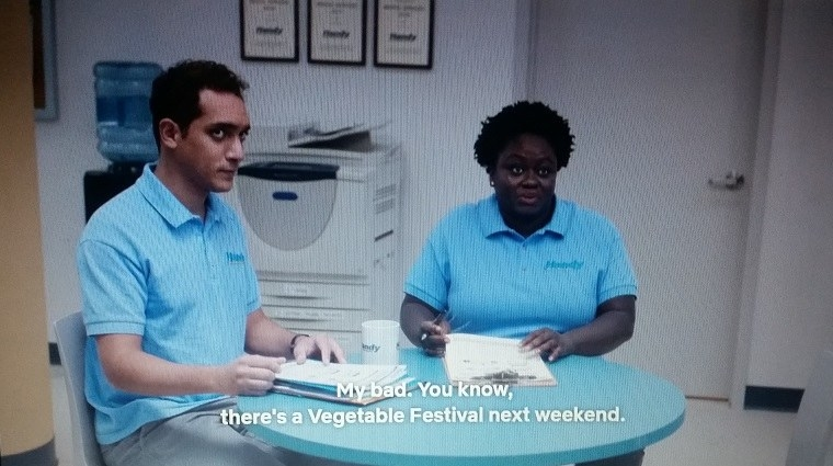 Omar and Stacie are sitting down at a blue table when Stacie mentions a Vegetable Festival.