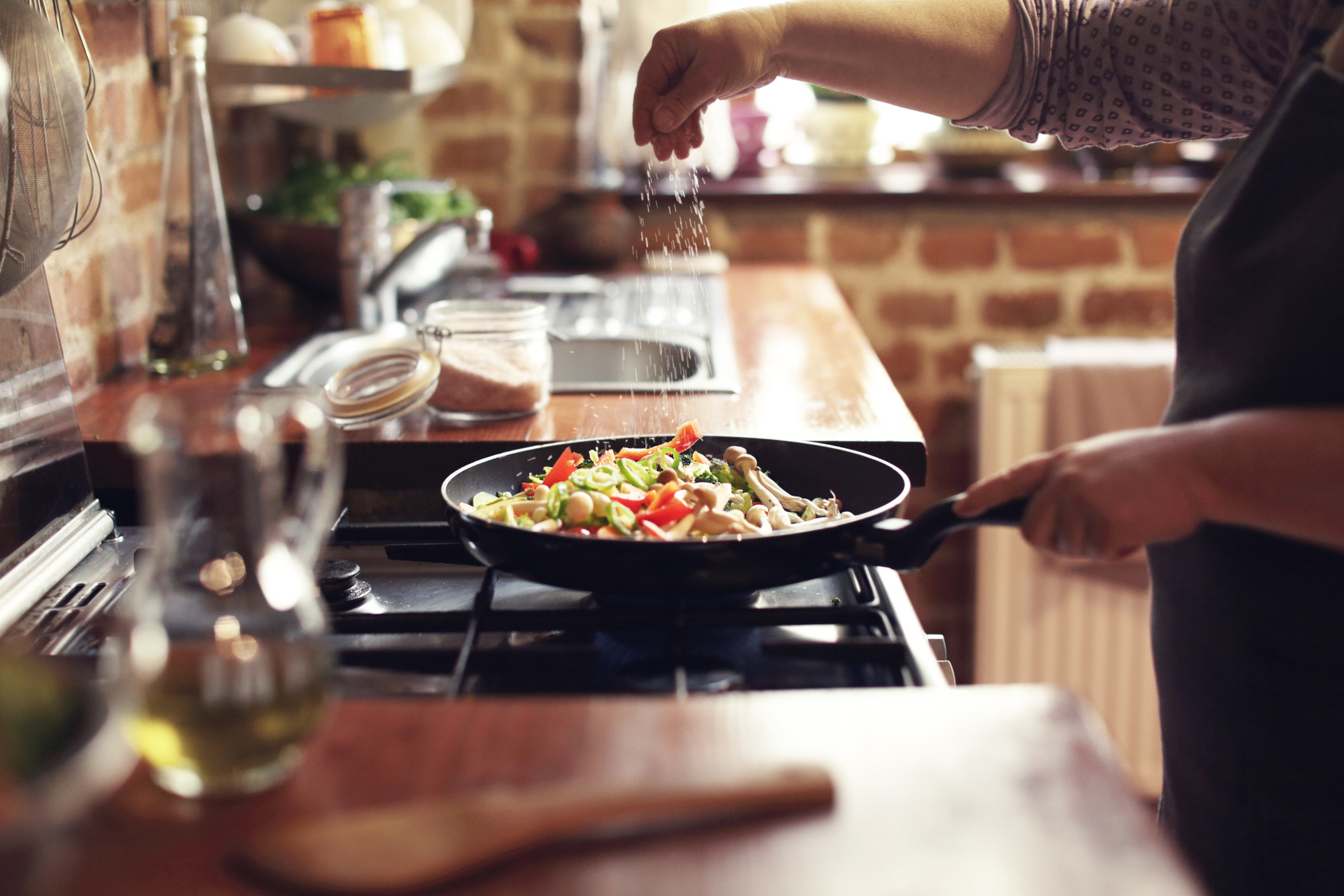 A woman salting her vegetables as they cook in the pan.