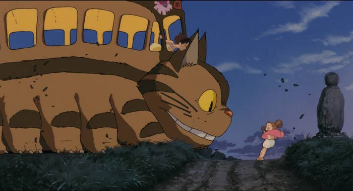 A bus in the form of cat staring at a little girl while a girl standing inside the bus looks out from the window.