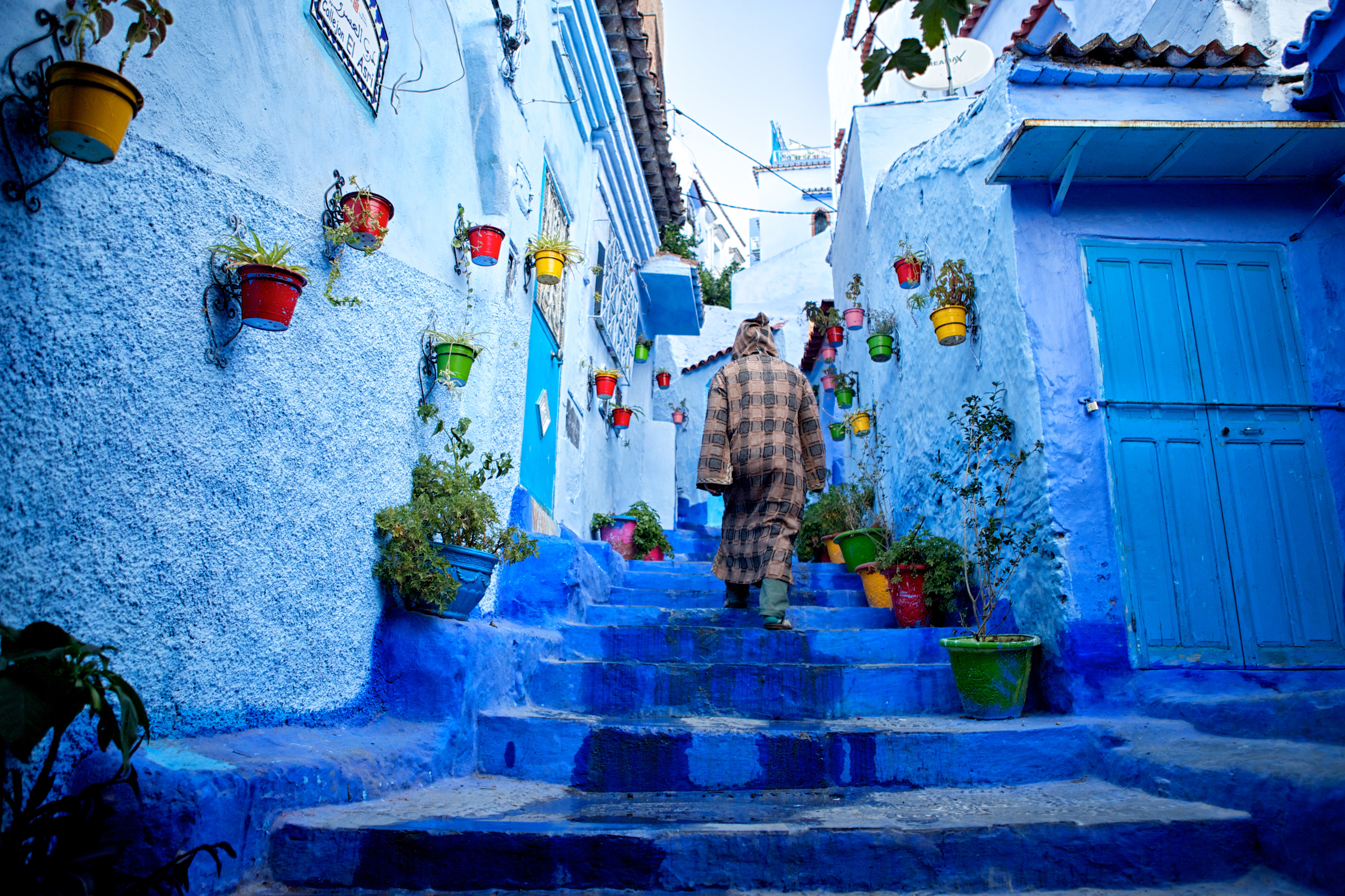 Man walks up the blue steps of a narrow street in the blue-washed Chefchaouen, Morocco. This town is known for being painted in exclusively one color (blue).