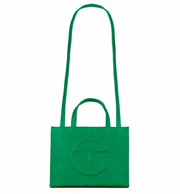 tote bag made of green faux leather with the brand's e-shaped logo on the front and a long handle for wearing across the shoulder plus regular wrist handles