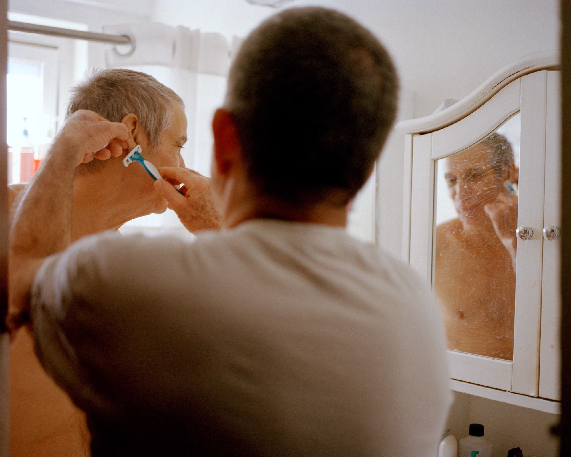 A younger man shaves an older man reflected in the mirror in a bathroom