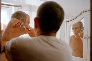 A younger man shaves an older man in the mirror in a bathroom