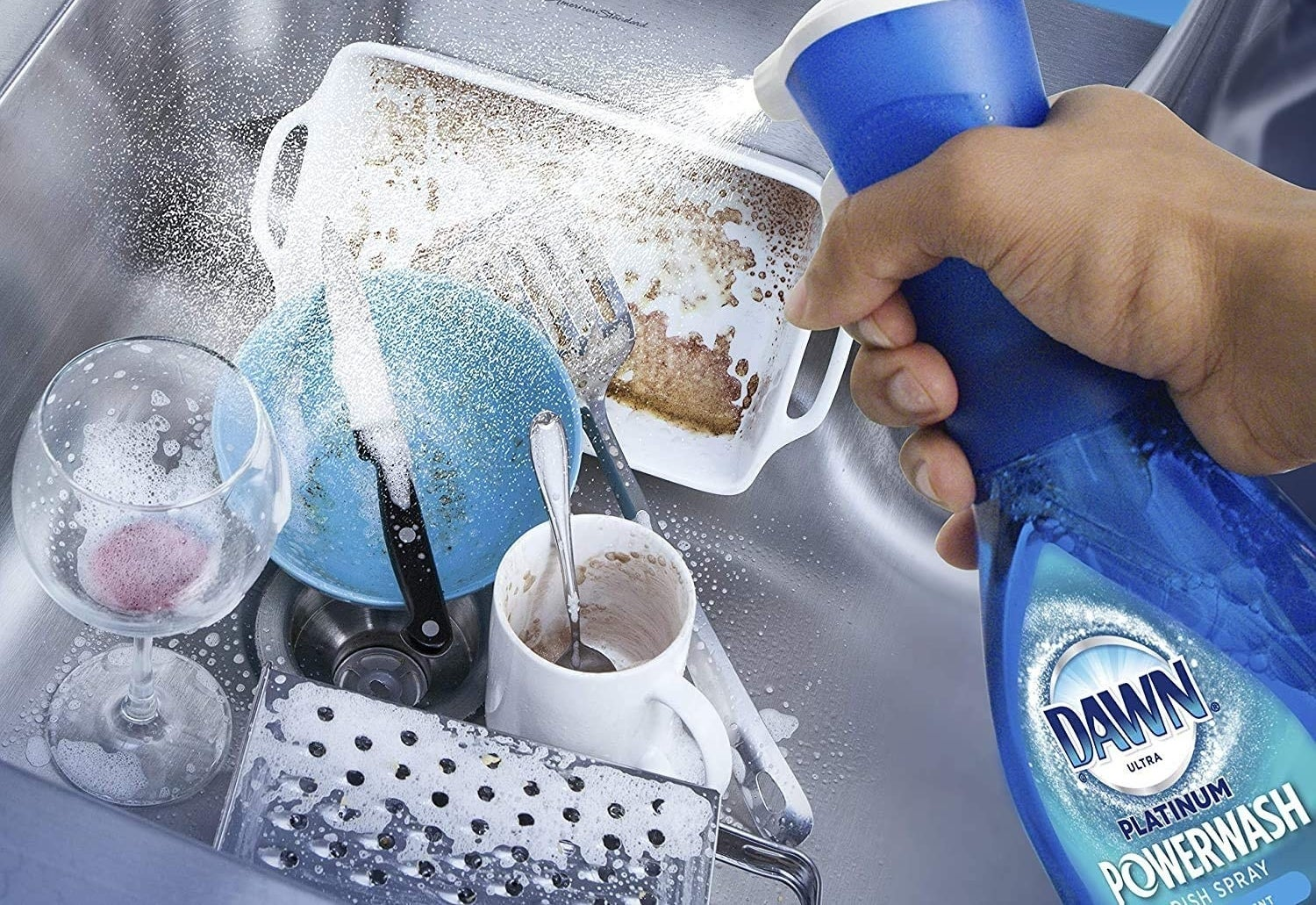person spraying a pile of dishes