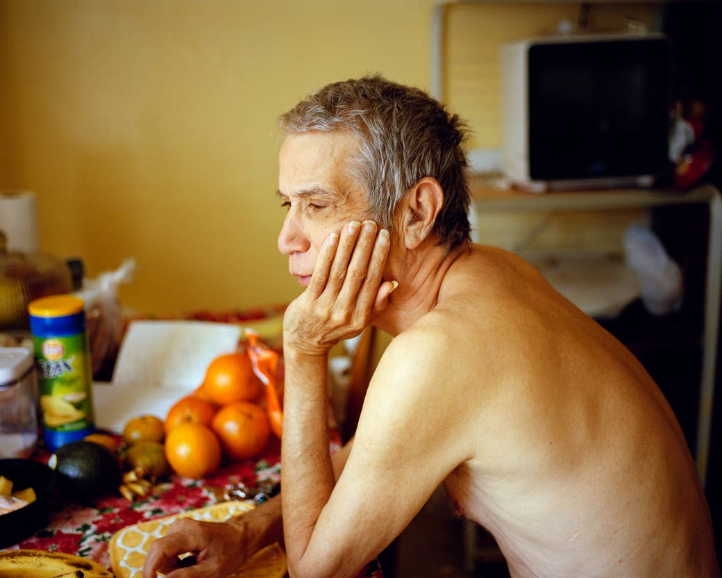 A man with long fingernails leans on a table with oranges and chips