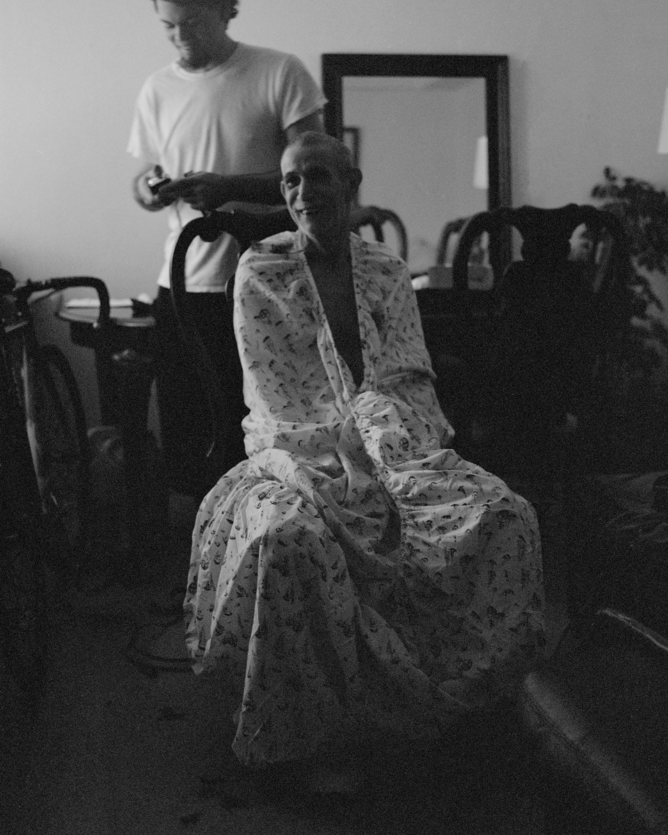 The photographer's father wrapped in a sheet, seated in their house