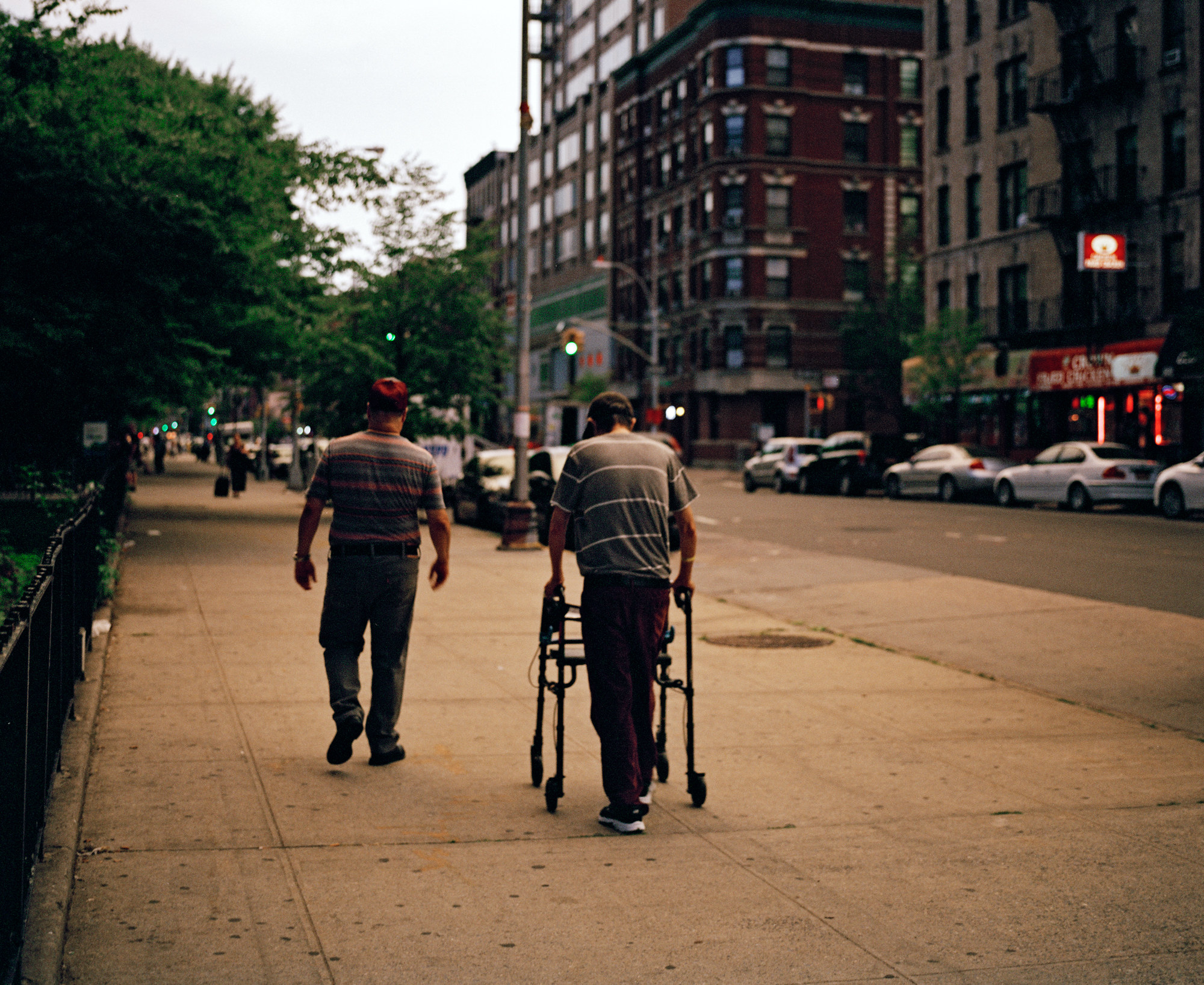 The photographer's father using a walker to walk down the street