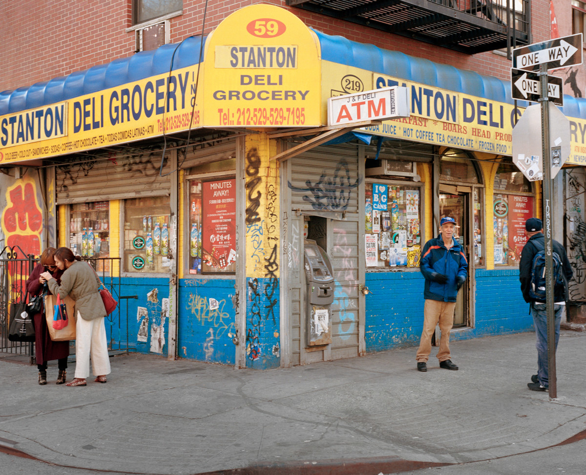 The photographer's father standing in front of a bodega in New York City