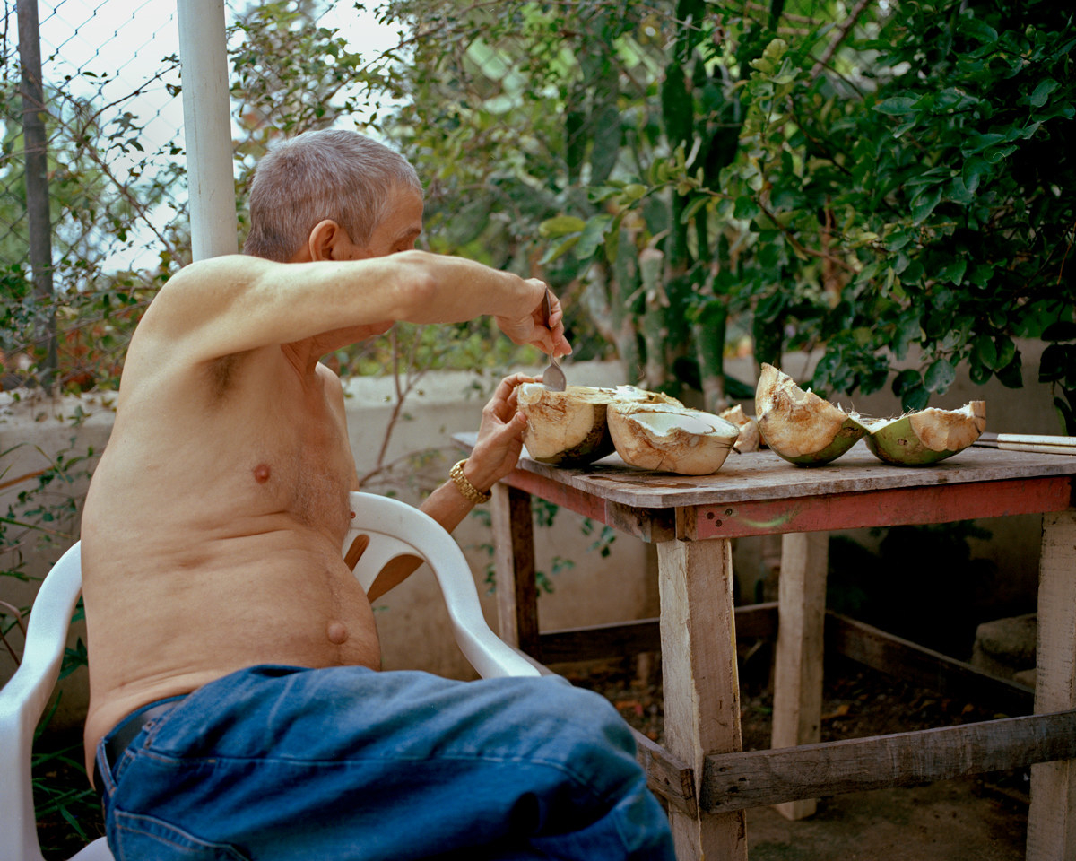 The photographer's father scooping flesh out of a coconut