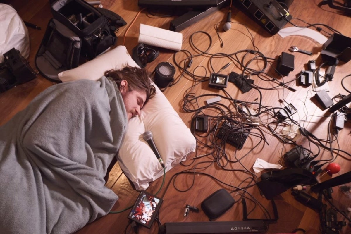 Bo rests his head on a pillow on the floor with a blanket wrapped around him and tons of wires and electrical equipment surrounding him