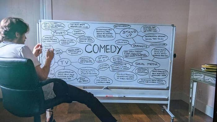 """Bo sits in front of a whiteboard with comedy written in the middle and bubbles with words like """"TV,"""" """"social media,"""" """"stand up,"""" and """"podcasts"""" branching off into other subcategories"""