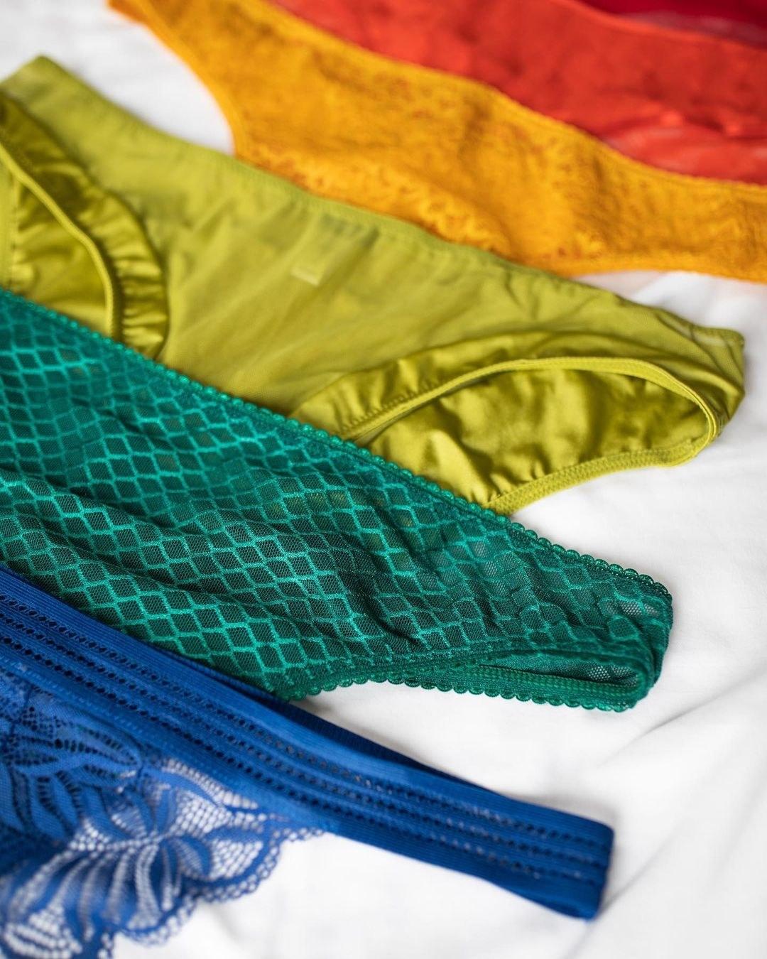 blue, green, yellow, and orange underwear on a bedsheet