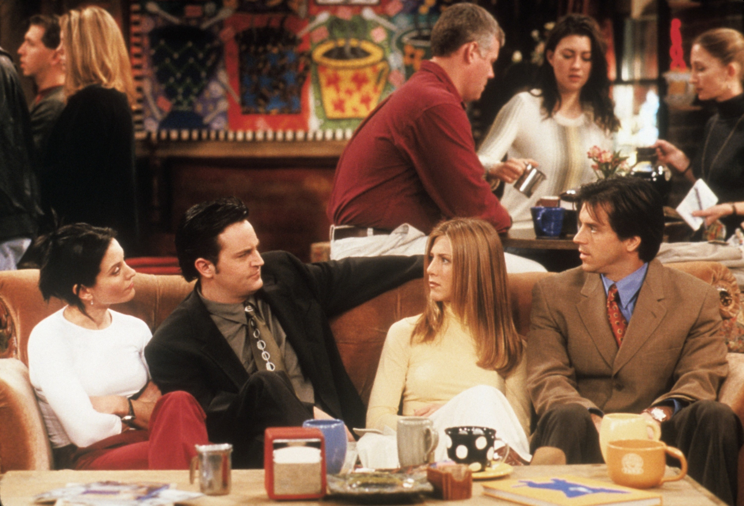 """Monica, Chandler, Rachel, and her date sitting on the couch at Central Perk on """"Friends"""""""