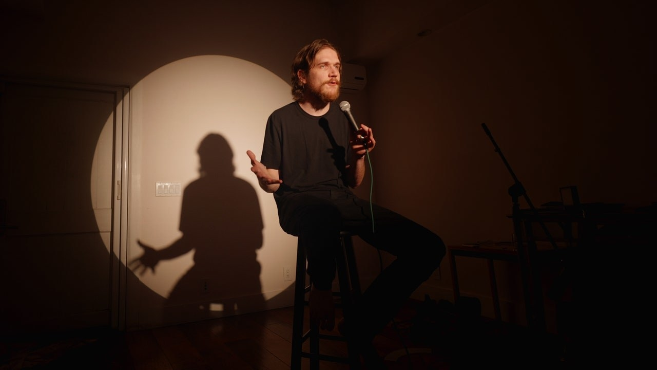 Bo sits down at a stool with a microphone in his hand as a spotlight illuminates him