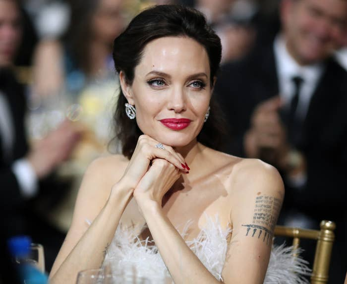 Angelina sits at a table with her arm tattoos visible