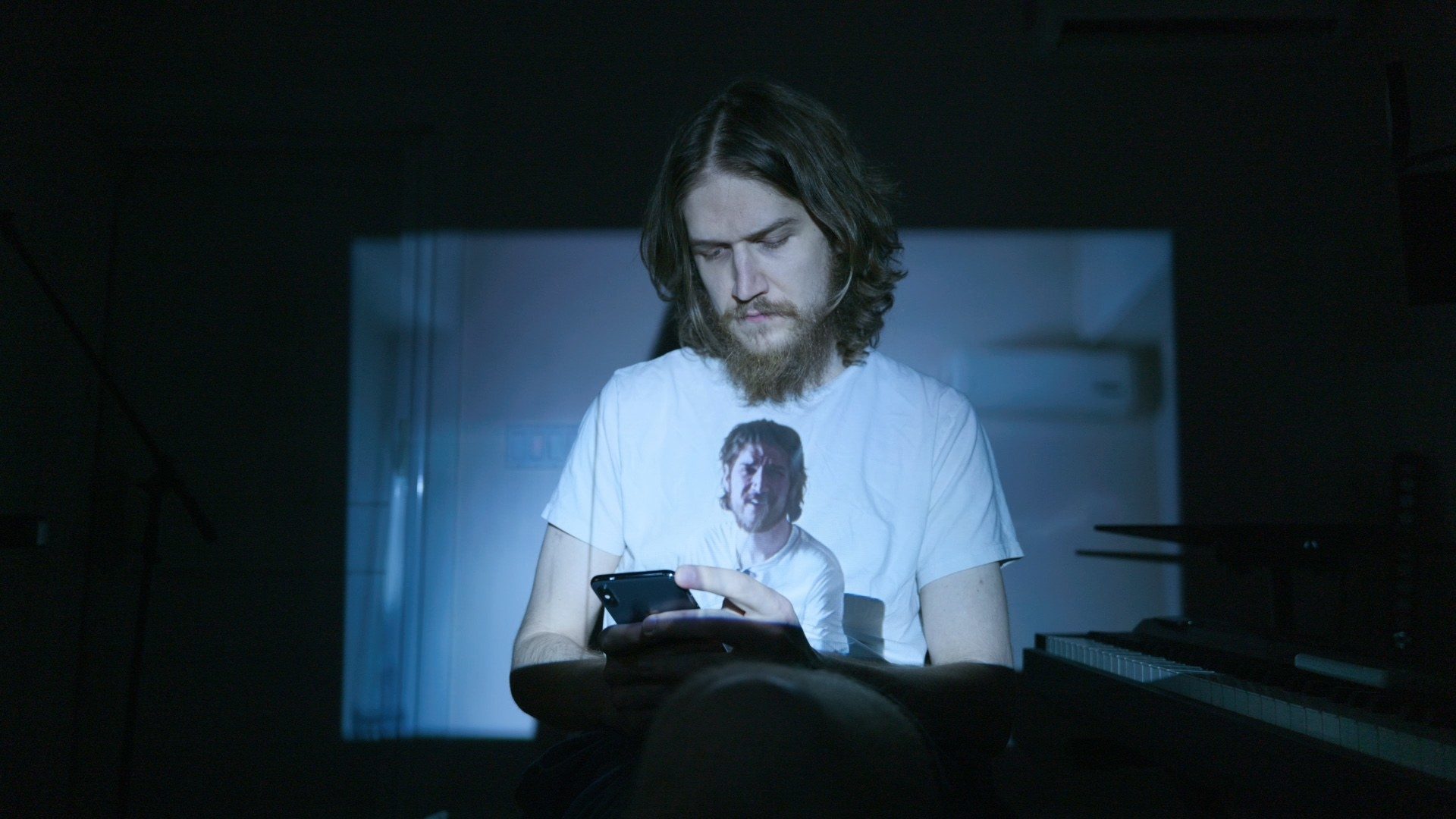 Bo looks down at his phone while a vide of Bo reflects onto his shirt