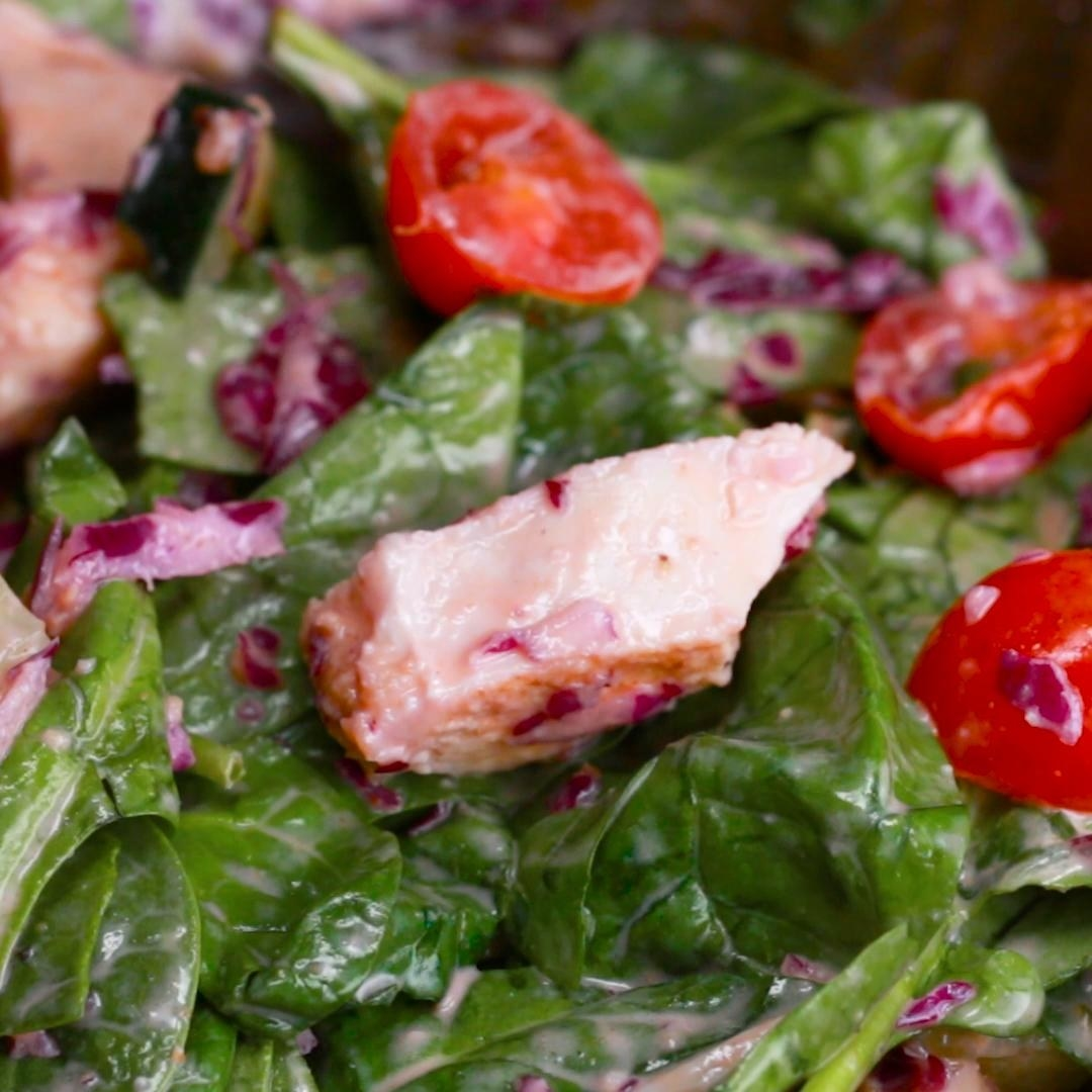 Greens topped with chicken, tomatoes, and a creamy dressing