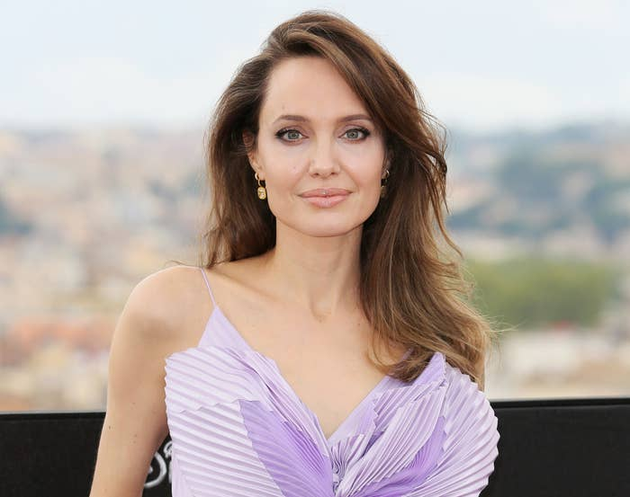 Angelina smiles while wearing a pleated lilac top