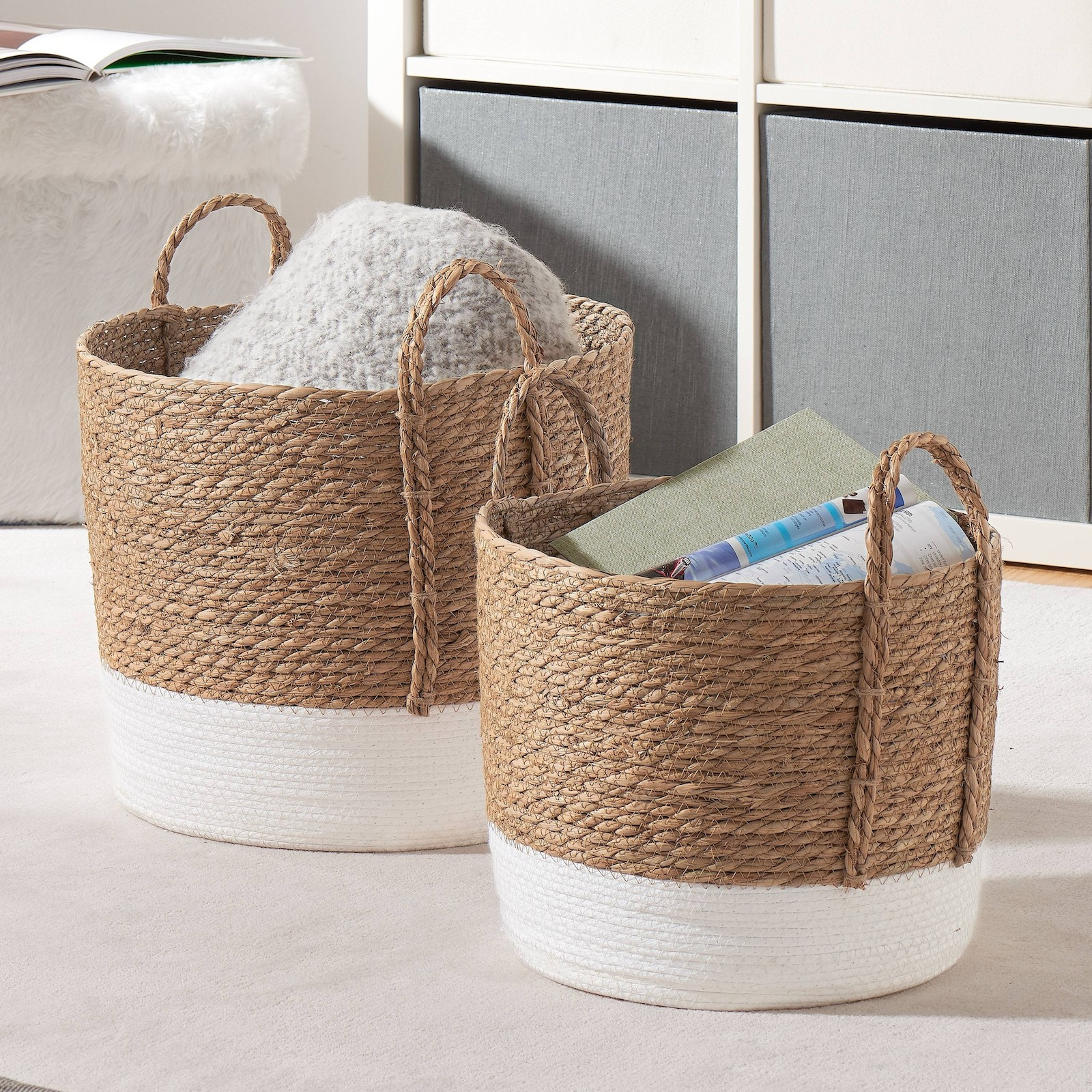 The two baskets with white bottoms and natural tops holding extra blankets and books