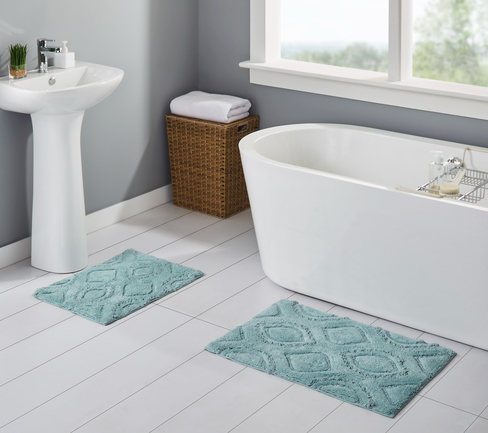 The rug set in a bathroom with the smaller rug underneath a sink and the larger rug just outside a bathtub