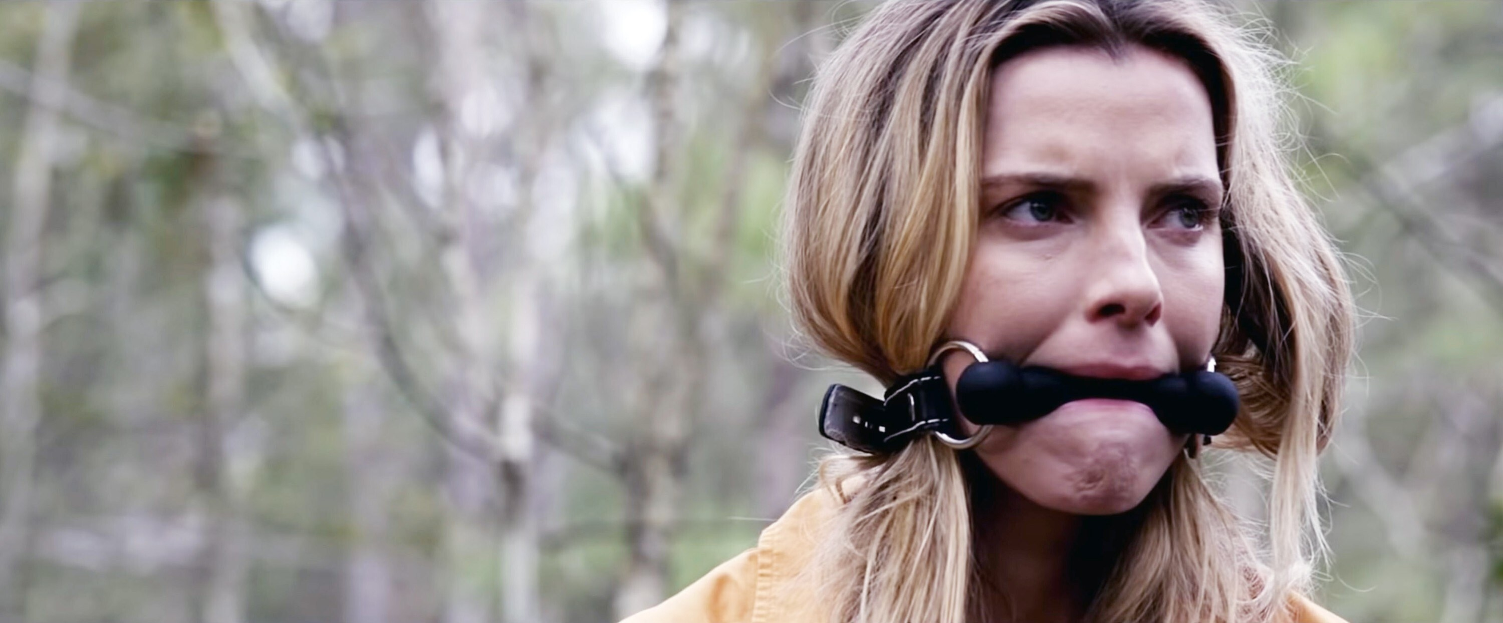 Betty Gilpin with her mouth gagged
