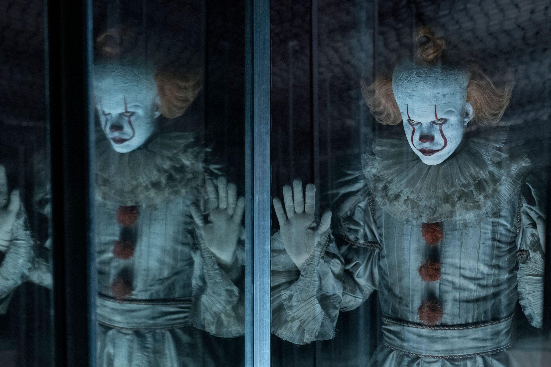 Bill Skarsgard as Pennywise looking through a funhouse mirror