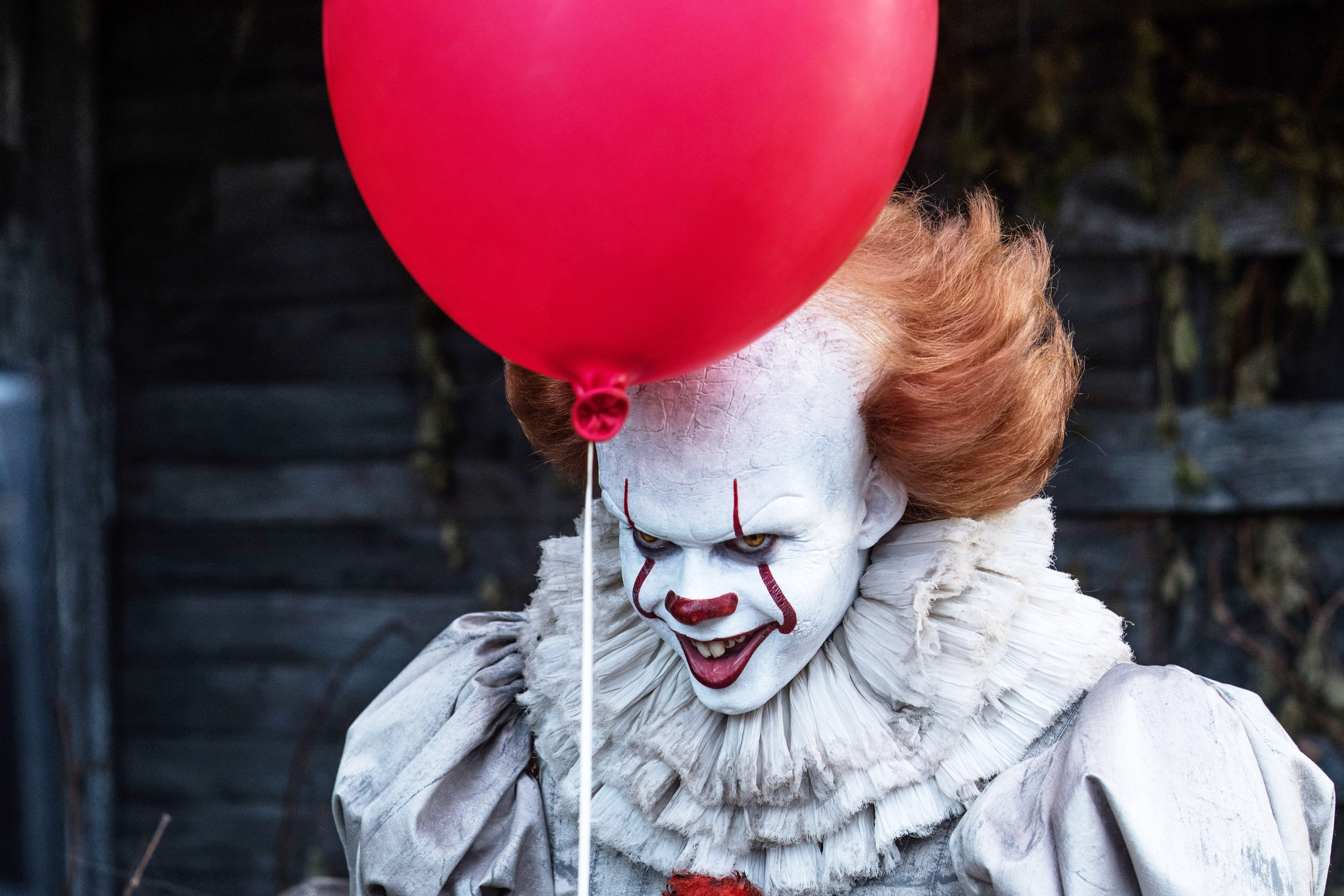 Bill Skarsgard as Pennywise with a red balloon