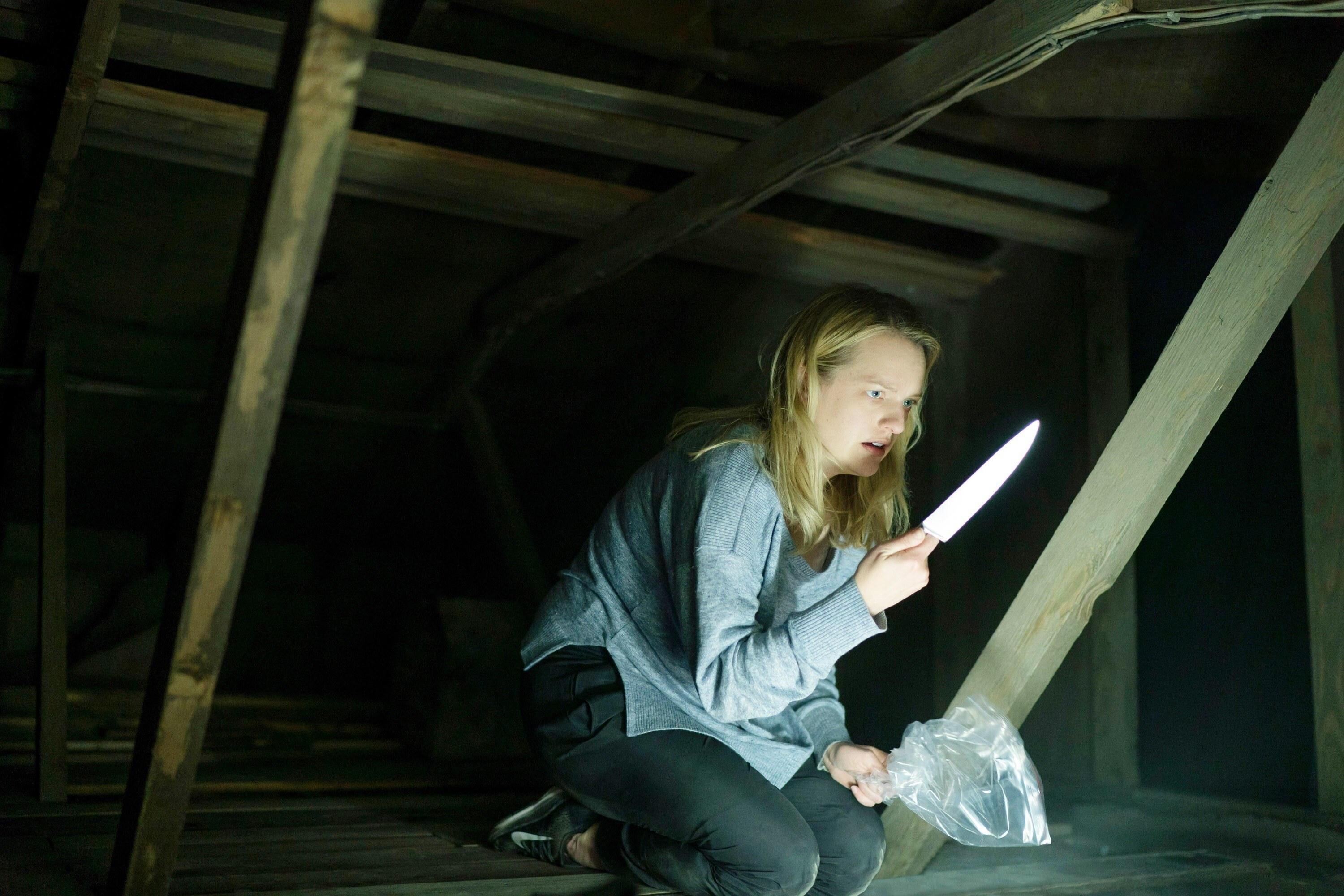Elisabeth Moss in an attic with a knife