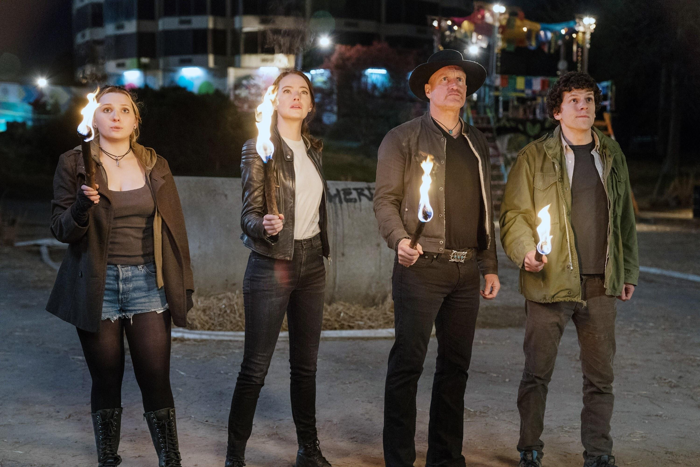 Abigail Breslin, Emma Stone, Woody Harrelson, and Jesse Eisenberg hold torches