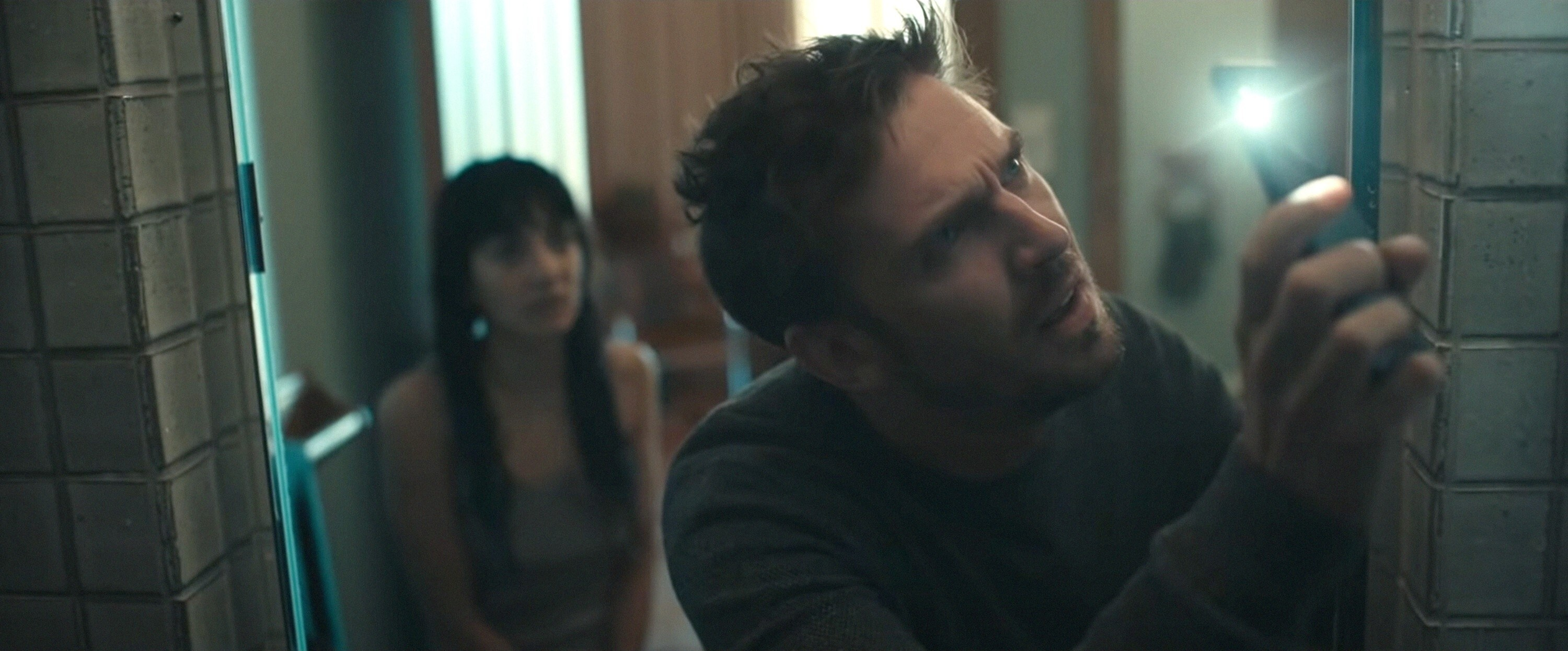 Sheila Vand and Dan Stevens use his iPhone light to investigate something
