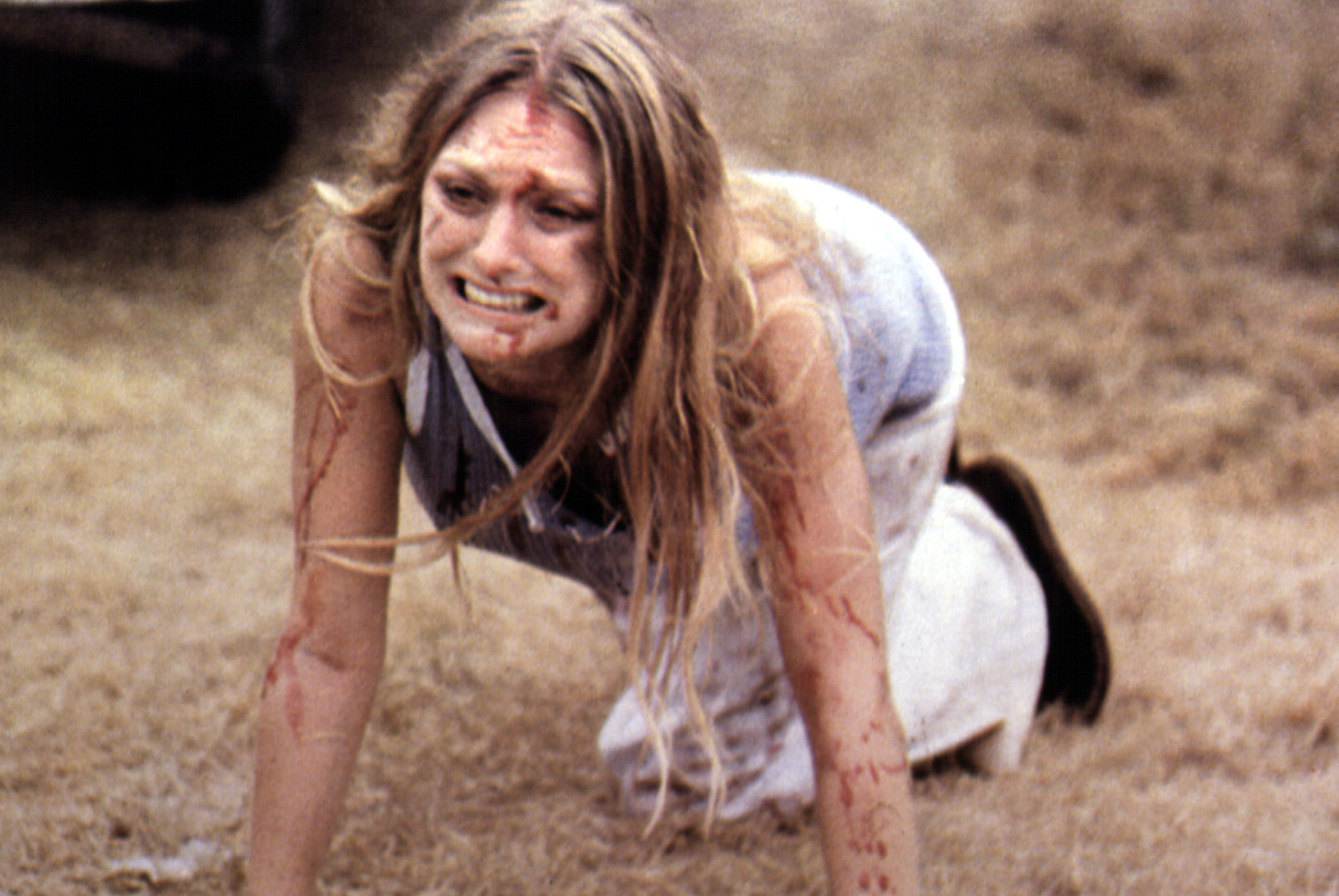 Marilyn Burns crawls on the ground bloody