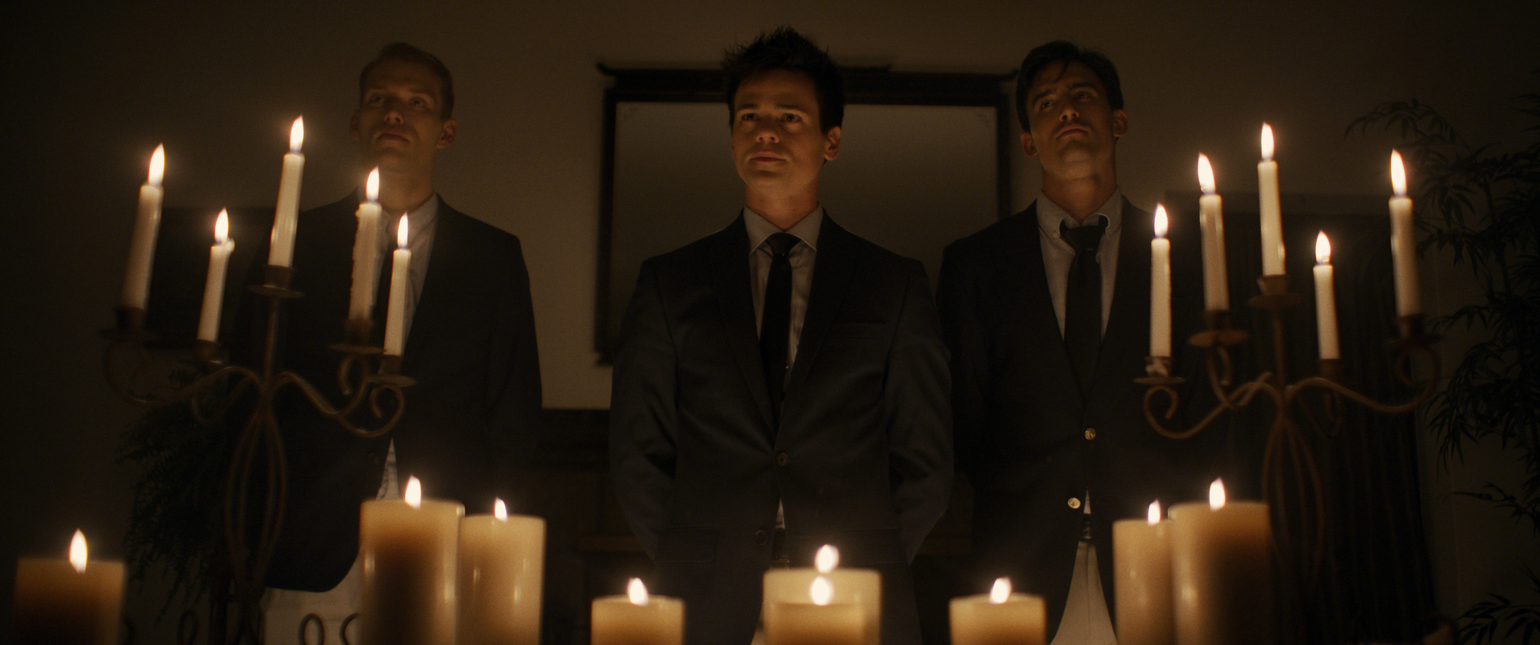 Cameron Cowperthwaite, Aaron Dalla Villa, and Jesse Pimentel stand behind a number of candles